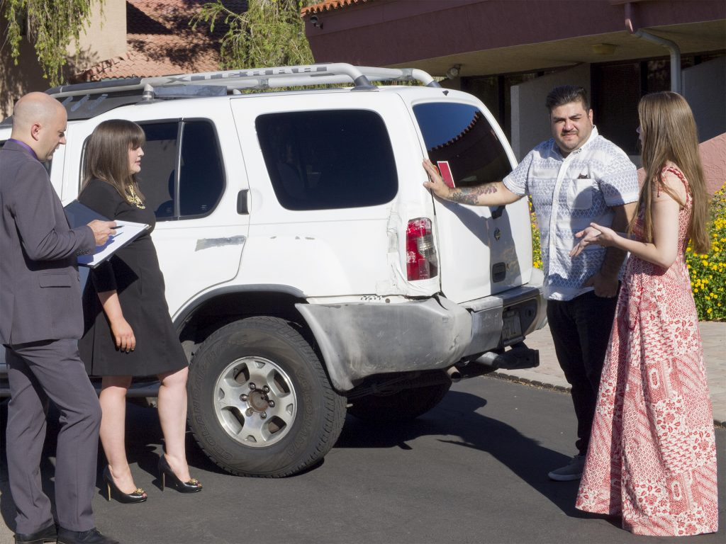 Kel and Chandra review the vehicle damage for two clients