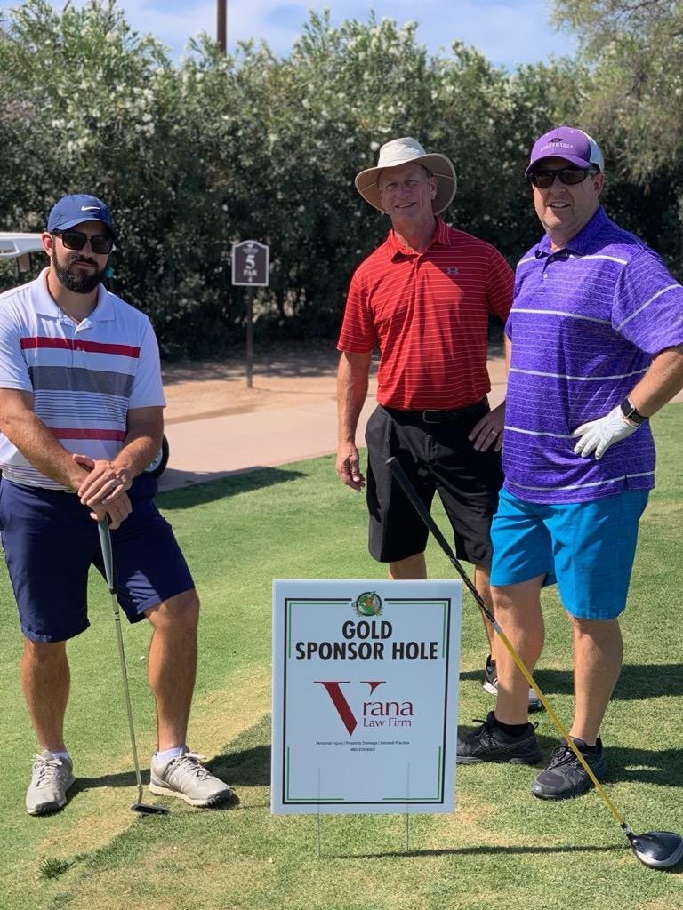 Golfers standing around Vrana Law Firm sponsored golf hole at annual Greenfield Elementary Dads Club tournament
